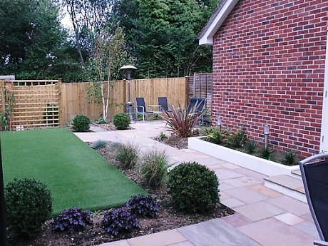 Sandstone paving, patio and artificial lawn